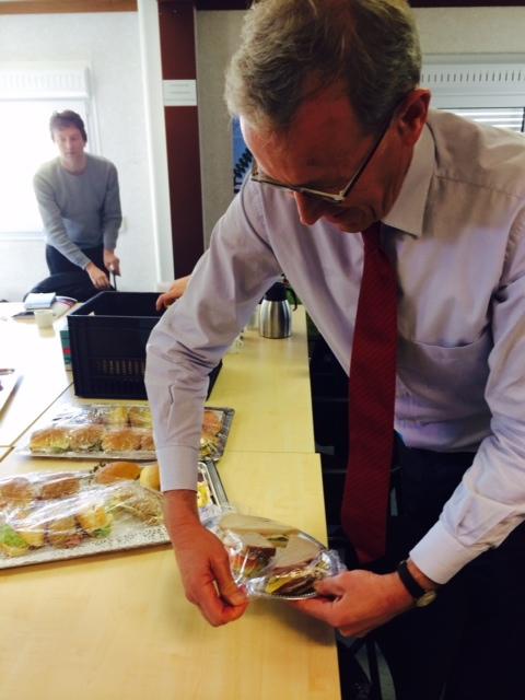 De bestuursvoorzitter serveert de broodjes